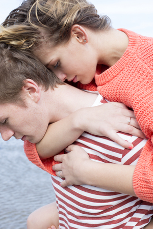 cuddled: Close up of a beautiful young couple at the beach. They are wearing casual clothing and are cuddled in together.