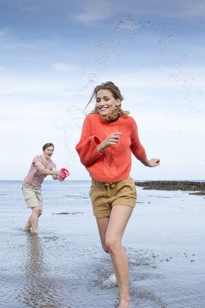 he she: Portrait of a beautiful young couple at the beach. He is holding a bucket and splashing her as she runs away from him. Stock Photo