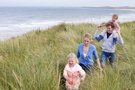 small child: A young family of four walking through long grass next to the beach. They are wearing casual clothing and are smiling.