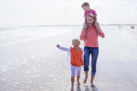 madre soltera: Madre soltera joven en la playa con su hijo e hija. Ellos se ríen y se descalzo en el agua. Foto de archivo