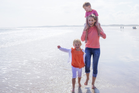 single family: Young single mother at the beach with her son and daughter. They are laughing and are barefoot in the water.