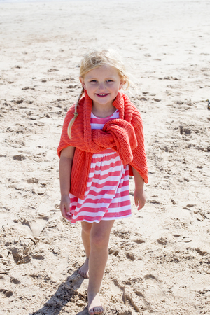 small girl: Little girl on the beach smiling at the camera. Stock Photo
