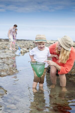 ni�os jugando: Young family at the seaside searching for creatures in rock pools. The young boy and his mother are the focus with the father and daughter in the background.