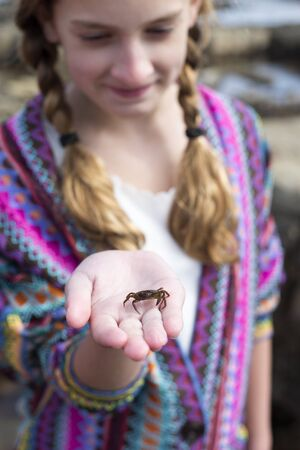 small girl: Young girl holding a crab in her hand at the seaside. Stock Photo