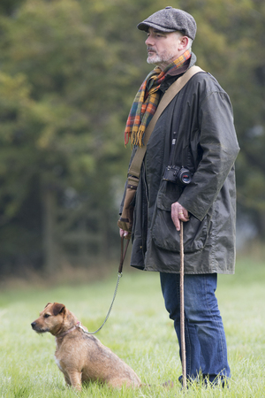 man's best friend: Man and his dog looking across the field during a walk on a cold foggy morning
