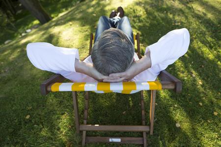 silla: Ariel vista de un hombre maduro se relaja en una tumbona en su jardín