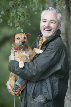 lifestyle outdoors: Portrait of a man holding his dog in a field. He is smiling for the camera.
