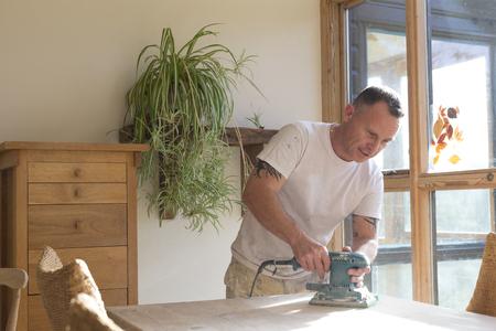 carpintero: Madera carpintero utilizando una lijadora eléctrica para suavizar la superficie de la mesa Foto de archivo
