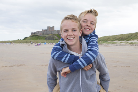 brothers: Teenage brothers at the beach with a castle in the background. They are wearing casual clothing and smiling at the camera.