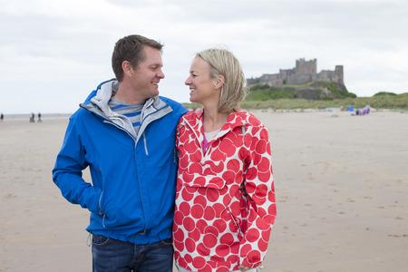 Älteres Paar zu Fuß am Strand. Sie haben ihre Arme umeinander und eine Burg kann im Hintergrund gesehen werden.