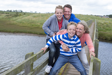bridge over water: Family of four on a bridge over water. They are wearing casual clothing and smiling at the camera. Stock Photo