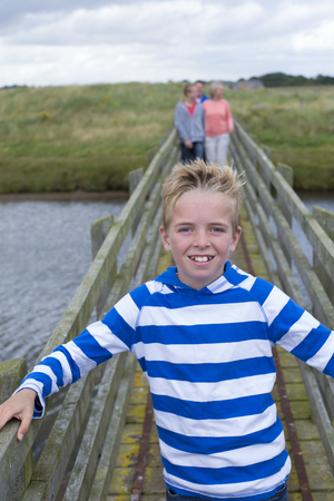 guy portrait: Portrait of a young boy on a bridge with his family in the background. He is smiling at the camera and wearing casual clothing. Stock Photo