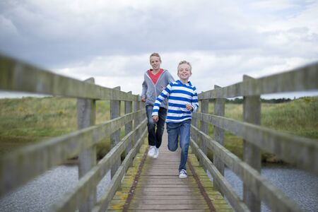 bridge over water: Two brothers running across a bridge over water in the countryside. They are wearing casual clothing and smiling. Stock Photo