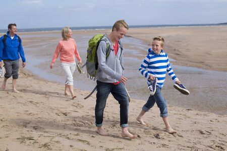 casual clothing: Family of four walking barefoot along the sand at the beach. They are wearing warm casual clothing. Stock Photo