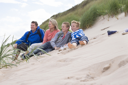 Family of four sitting on the sand dunes. They are wearing warm, casual clothing and looking out to sea.