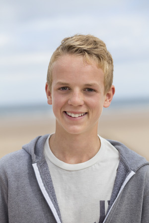 Portrait of a happy teenage boy at the beach. He is looking at the camera and smiling and wearing casual clothing.