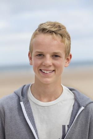 ojos azules: Retrato de un adolescente feliz en la playa. Él está mirando a la cámara y sonriendo y vistiendo ropa casual.