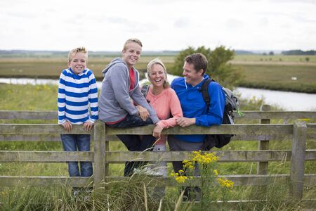 bridge over water: Happy Family of four on a bridge over water in the countryside. They are wearing casual clothing and smiling. Stock Photo