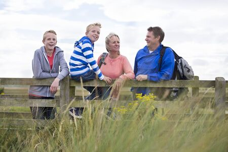 mama e hijo: Familia de cuatro miembros feliz en un puente. Se trata de llevar ropa casual y mirando a los alrededores.