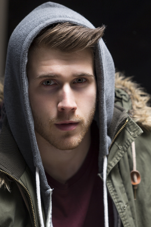poses: Close up portrait of a young man posing with his hood up. Stock Photo