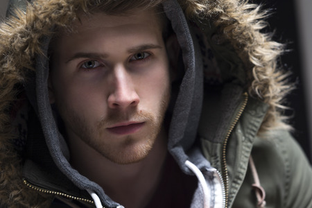 Close up portrait of a young man posing with his hood up. Stock Photo