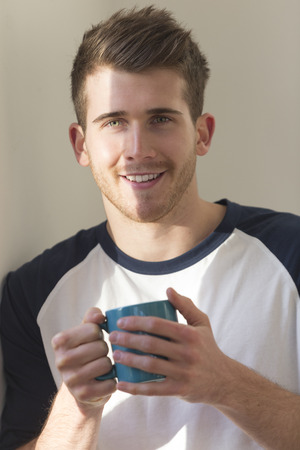 only man: Portrait of a man holding a hot drink. He is smiling at the camera. Stock Photo