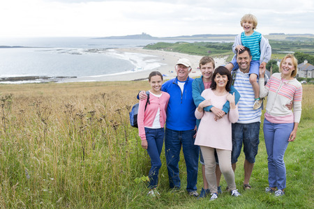 childen: A family are standing on the sand dunes, they are all smiling and looking at the camera.