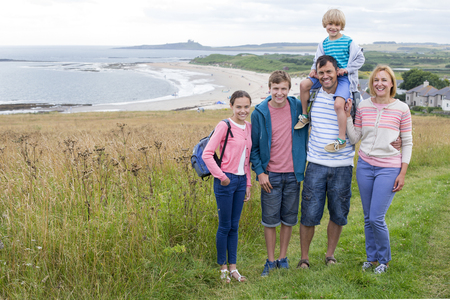 childen: A family of five are stood on the sand dunes. They are all smiling looking at the camera. Stock Photo