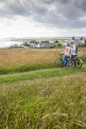 sand dunes: A couple are stood on the sand dunes with their bikes, they have stopped to enjoy the view. Stock Photo