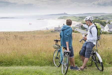A father and son are on the sand dunes with their bikes. They have stopped to talk and enjoy the view.