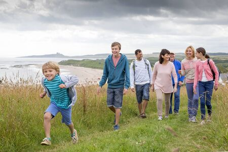 all: A family are walking on the sand dunes, they are all smiling and talking amounst themselves. Stock Photo