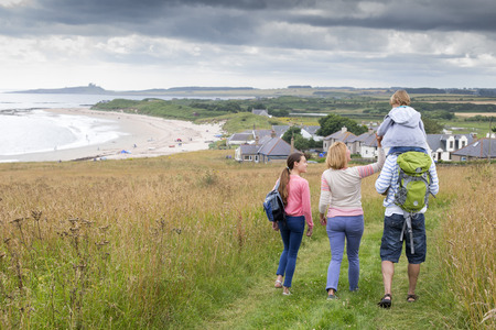 childen: A fmaily of four are walking along the sand dunes. The little boy is getting carried on his fathers shoulders.