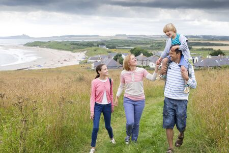 personas hablando: Una familia de cuatro personas est� caminando en las dunas de arena juntos. El hijo est� sentado sobre los hombros de padres. Todos ellos se ven felices y est�n sonriendo.