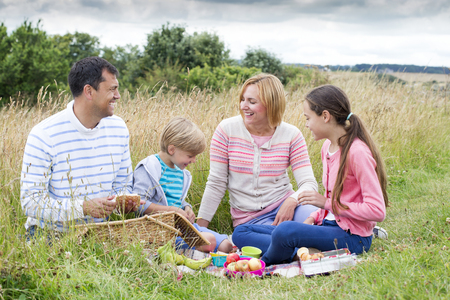 childen: A family of four are sat on the sand dunes having a picnic