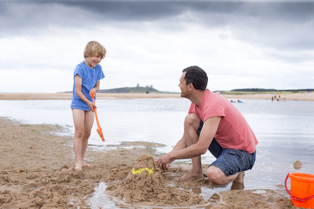 quality time: A father and son are building sand castles on the beach