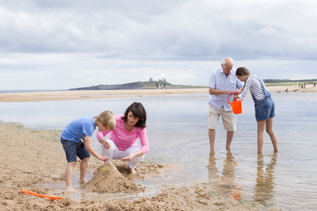 Nonni e nipoti stanno giocando insieme sulla spiaggia. Sembrano tutti felici giocando con la sabbia e acqua.