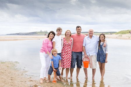 childen: A family are on the beach with their feet in the water. They are all smiling, looking at the camera.