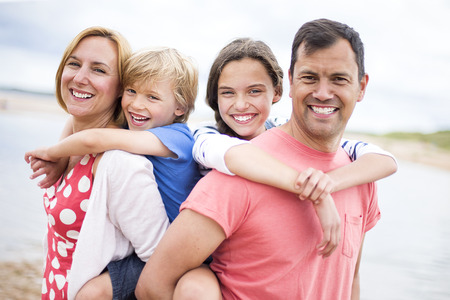 Eine vierköpfige Familie sind am Strand zusammen, die Kinder auf ihre Eltern den Rücken. Sie sind alle lächelnd in die Kamera schaut.