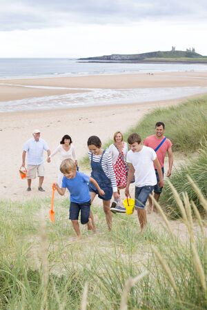 childen: A family are at the beach together, they are all walking up the sand dunes, smiling and talking.