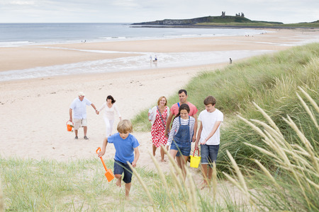 family life: A family are walking up the sand dunes, leaving the beach. They are all smiling and talking with each other.