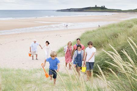 convivencia familiar: Una familia está caminando por las dunas de arena, dejando la playa. Todos ellos están sonriendo y hablando entre sí.
