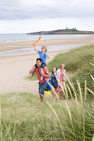 childen: A family of four are walking up the sand dunes toegther, leaving the beach. The little boy is on his dads shoulders laughing.