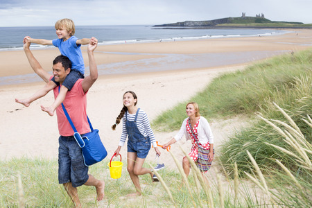 childen: A family of four are leaving the beach together. The little boy i on his dads shoulder smiling. Stock Photo