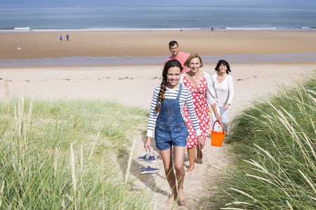 childen: A family of four are walking up the sand dunes leaving the beach. They all look happy and are smiling.