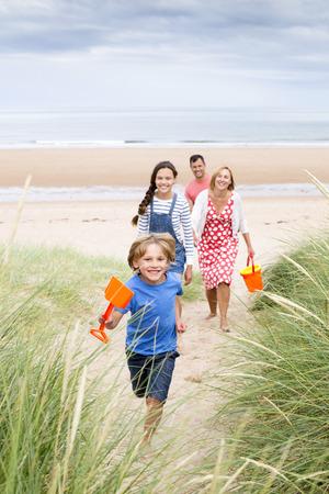 convivencia familiar: Una familia de cuatro personas está caminando por las dunas de arena que salen de la playa. El niño pequeño se está ejecutando primero sonriendo a la cámara.
