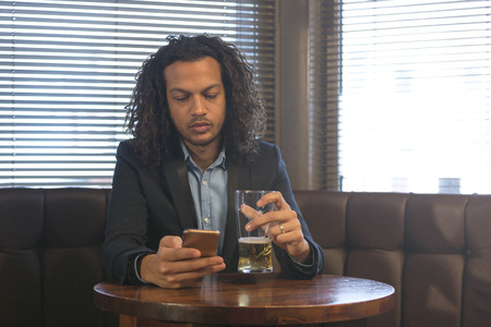typically british: Young man using his smartphone whilst enjoying a beer in a bar. Stock Photo
