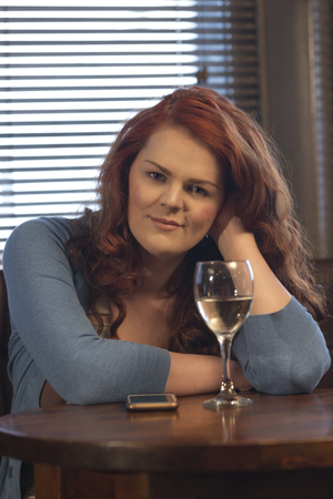 Attractive young woman sitting in a pub with a glass of wine and her smartphone. She is smiling at the camera.