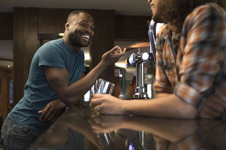 typically british: Young man standing at the bar talking to the bartender Stock Photo