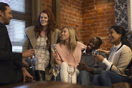 small group: Small group of friends sitting in a bar, enjoying some drinks whilst chatting together. Stock Photo