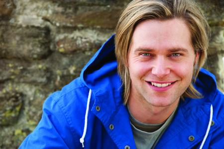ojos verdes: Hombre joven atractivo que se sienta afuera. El está sonriendo a la cámara.